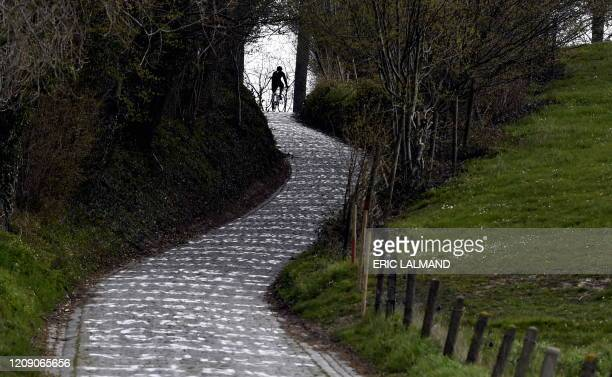 """Person rides a bike on April 3 on the Koppenberg climb in Oudenaarde, usually a part of the track of """"Tour of Flanders"""" cycling race. - The 104th..."""