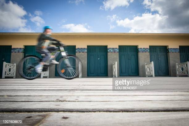 """Person rides a bike on """"Les Planches"""" in Deauville, Normandy, on March 18, 2020 after a strict lockdown came into effect in France to stop the spread..."""