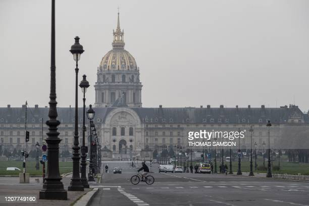 Person rides a bike on March 20, 2020 past the Alexandre III Bridge with the Hotel des Invalides in Paris in the background, on the fourth day of a...