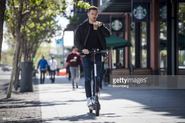 A person rides a Bird Rides Inc shared electric scooter in San Francisco California US on Thursday May 3 2018 City officials eager to do something...