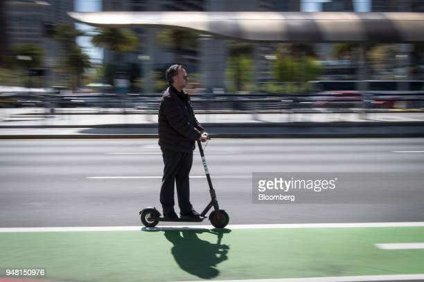 A person rides a Bird Rides Inc shared electric scooter on the Embarcadero in San Francisco California US on Friday April 13 2018...