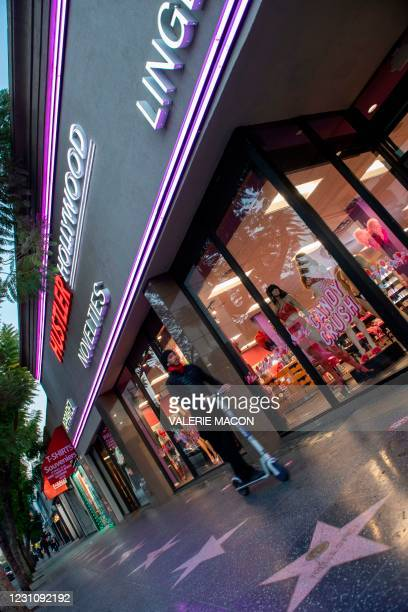 Person rides a scooter by the Hustler Hollywood store on February 10, 2021 in Hollywood, California. - US porn mogul Larry Flynt, best known as the...
