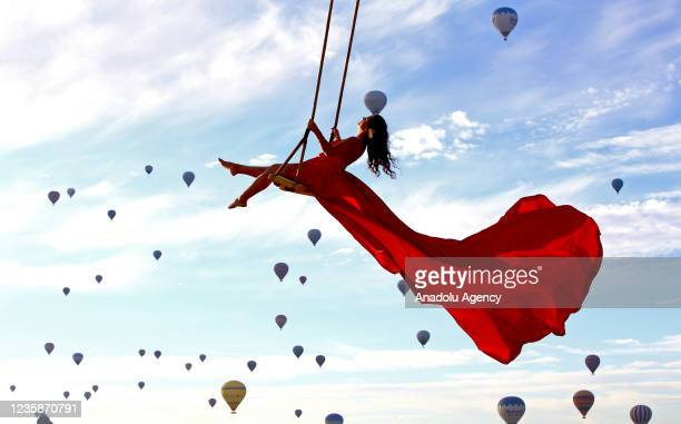 Person rides a swing hanging from a crane with hot air balloons fly in the background in Nevsehir, Turkey on October 14, 2021. Tourists and those who...