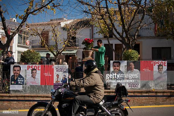 A person rides past electoral posters of main candidates for the upcoming December 20 general election on December 4 2015 in Ronda southern Spain...