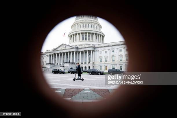 Person rides past the Capitol building as negotiations on a COVID-19 economic bailout continue on Capitol Hill March 24 in Washington, DC. - US...