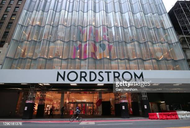Person rides past the Nordstrom department store decorated for Christmas on 57th Street on December 8, 2020 in New York City.