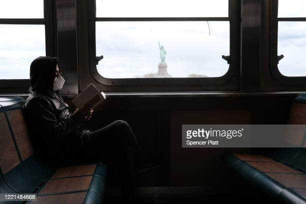 Person rides the Staten Island Ferry as it passes the Statue of Liberty on April 27, 2020 in New York City. Hospitals in New York City, which have...
