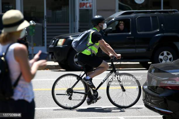 A person riding a bicycle wears a mask while riding on May 25 2020 in Westwood California Government guidelines encourage wearing a mask in public...