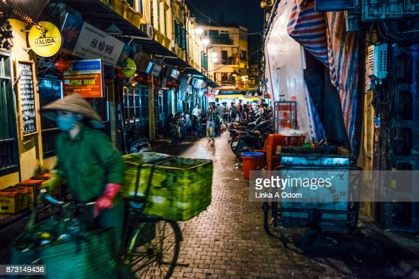 a person riding a bike through hanoi's old quarter. - south east asia stock pictures, royalty-free photos & images