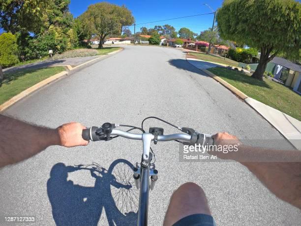 person riding a bycicle on a suburban city neighborhood road - rafael ben ari fotografías e imágenes de stock