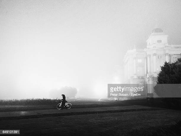 person riding bicycle by building against sky during foggy weather - boban stock pictures, royalty-free photos & images