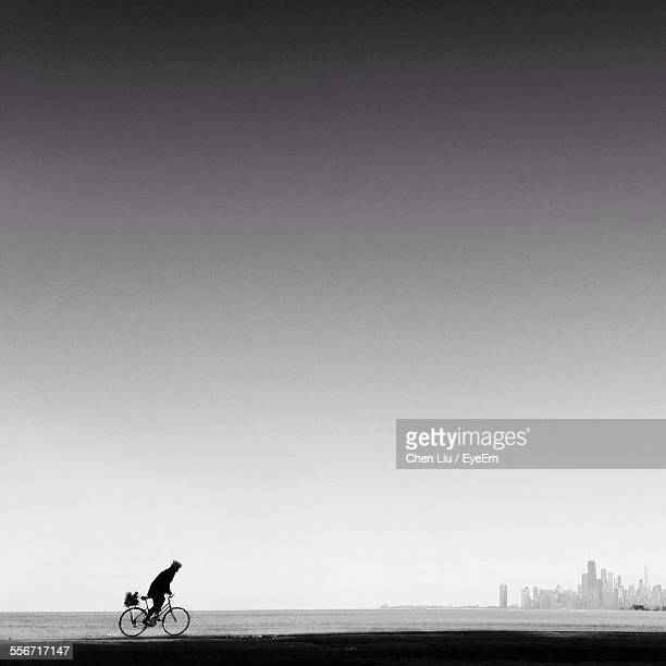Person Riding Bicycle On Beach Against Clear Sky