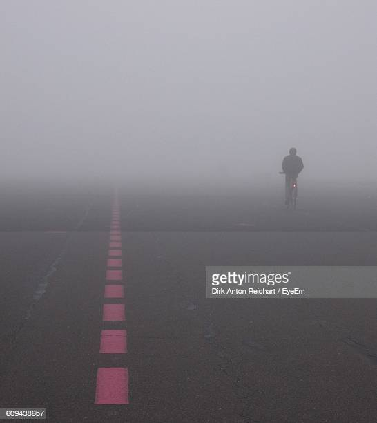 Person Riding Bicycle On Road During Foggy Weather