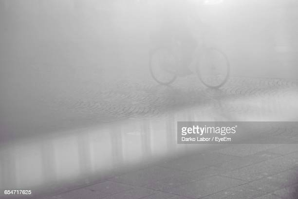 Person Riding Bicycle On Street During Foggy Weather