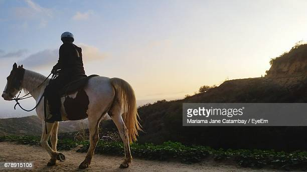 Person Riding Horse On Dirt Road Against Sky During Sunset