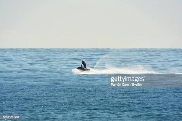 Person Riding Jet Boat On Sea Against Sky