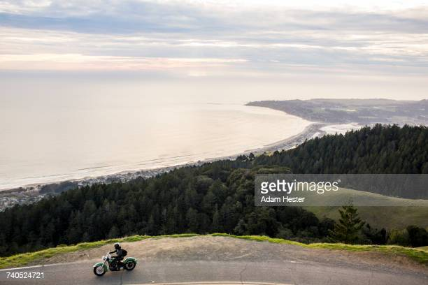 Person riding motorcycle at edge of cliff near ocean