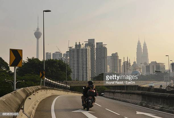 Person Riding Motorcycle On Road By Menara Kuala Lumpur Tower And Petronas Towers Against Sky