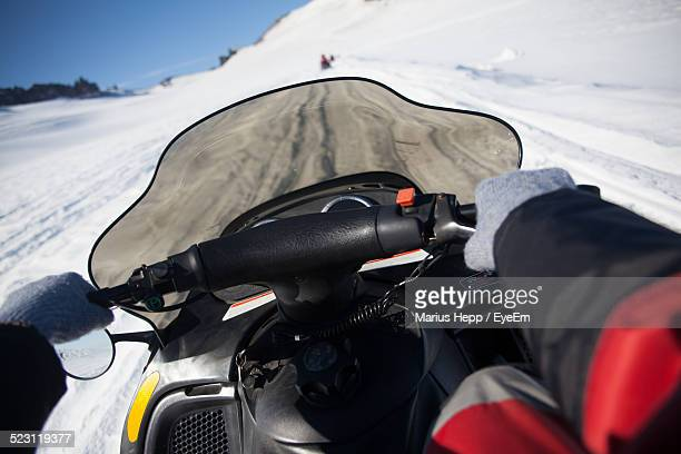 Person Riding Snowmobile On Snowy Field