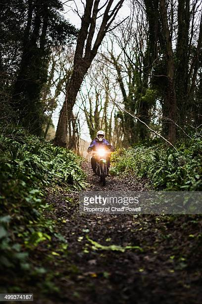 Person riding through a forest on a motorbike
