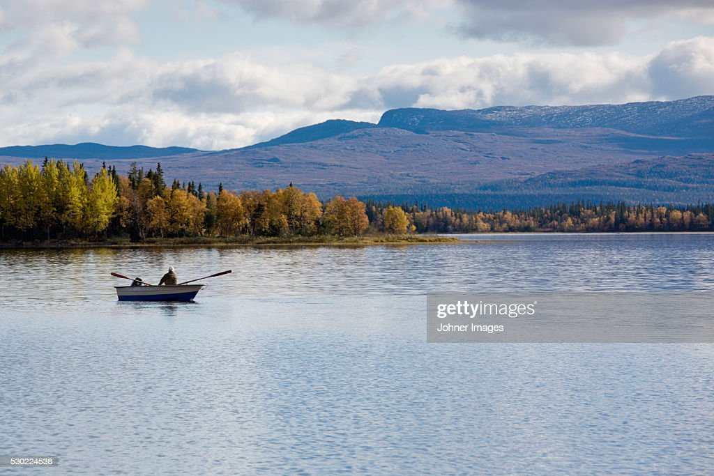 Person rowing on lake : Stock Photo