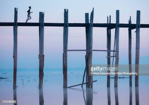 Person running across u bein bridge, Mandalay, Mandalay Region, Myanmar