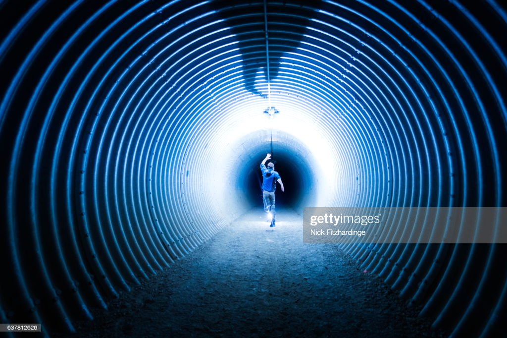 A person running inside a highway underpass at night in Winfield, Lake Country, British Columbia, Canada : Bildbanksbilder
