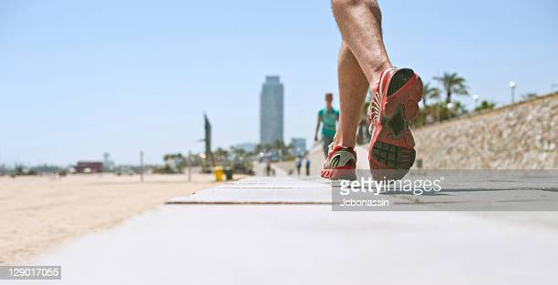 person running on road - jcbonassin stock pictures, royalty-free photos & images