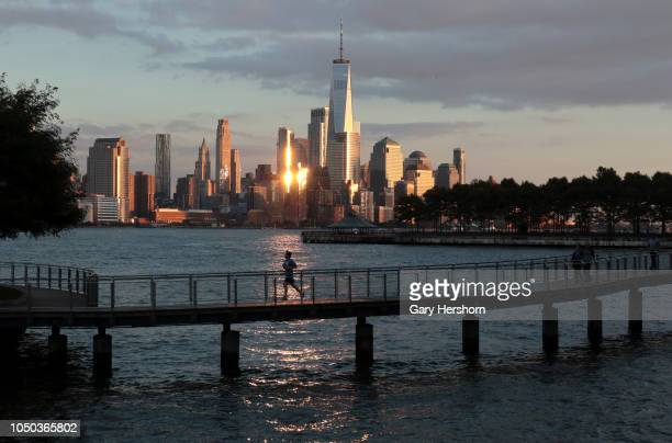 A person runs on a pier in front of the skyline of lower Manhattan and One World Trade Center in New York City at sunset on October 3 2018 as seen...