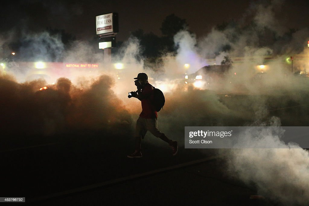 A person runs through a clowd of tear gas that police launched at demonstrators protesting the killing of teenager Michael Brown on August 17, 2014 in Ferguson, Missouri. Police shot smoke and tear gas into the crowd of several hundred as they advanced near the police command center which has been set up in a shopping mall parking lot. Brown was shot and killed by a Ferguson police officer on August 9. Despite the Brown family's continued call for peaceful demonstrations, violent protests have erupted nearly every night in Ferguson since his death.