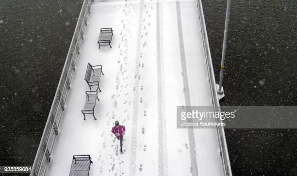 A person runs through snow and high winds along the Schuylkill River on March 21 2018 in Philadelphia Pennsylvania The fourth nor'easter in three...