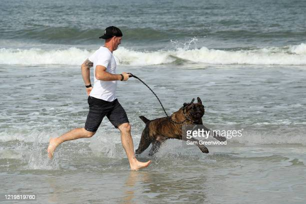 A person runs with a dog at the beach on April 19 2020 in Jacksonville Beach Florida Jacksonville Mayor Lenny Curry announced Thursday that Duval...