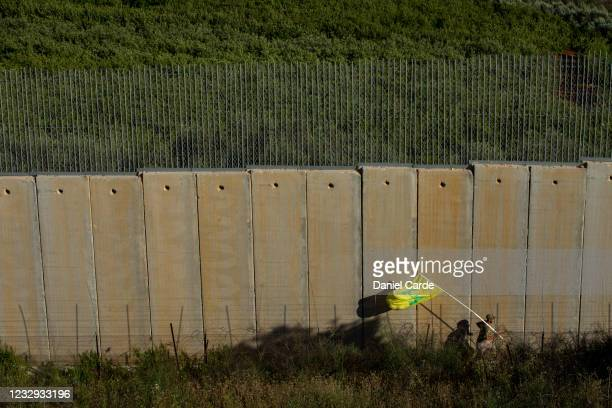 Person runs with a Hezbollah flag behind the Lebanon-Israel border wall during a demonstration to show solidarity with Palestinians on May 16, 2021...