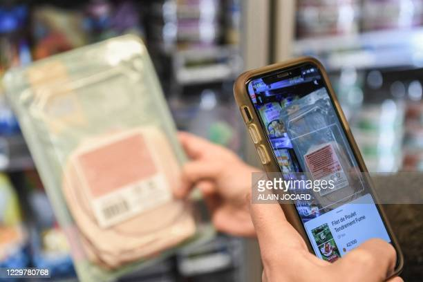 Person scans a product using the Yuka food and cosmetic scanner mobile phone application on November 25, 2020 in Paris. - The app uses product label...