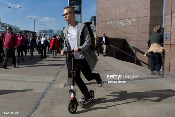 Person scoots and commuters and other pedestrians walk over London Bridge, the oldest of the capital's crossing over the river Thames between the...