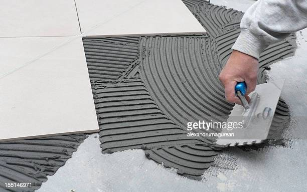 person scrapes concrete at a construction site - tiled floor stock pictures, royalty-free photos & images