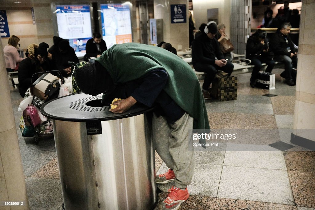 A person searches a garbage can at a Manhattan train station on December 14, 2017 in New York City. According to a new report released by the U.S. Department of Housing and Urban Development New York City's homeless population expanded by about 4 percent in 2017 as the number of homeless people nationwide grew to about 553,000.