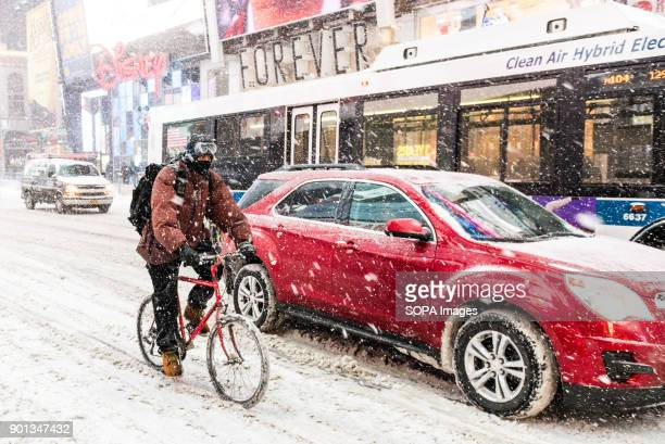 A person seen cycling during heavy snow storm in Times Square New York city is under heavy snow storm as a giant winter 'bomb cyclone' walloped the...
