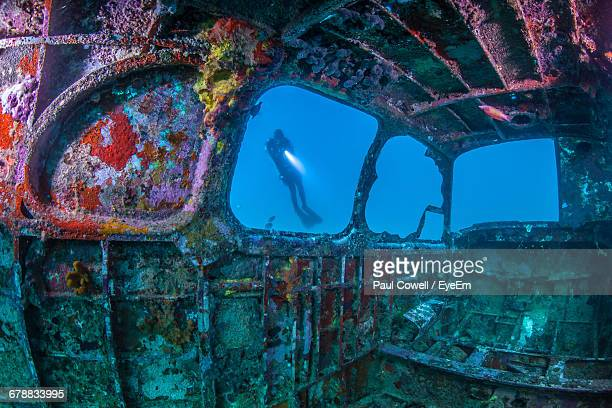 person seen through shipwreck in sea - shipwreck stock pictures, royalty-free photos & images