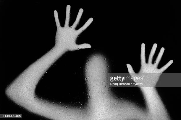 Person Seen Through Wet Glass Against Black Background