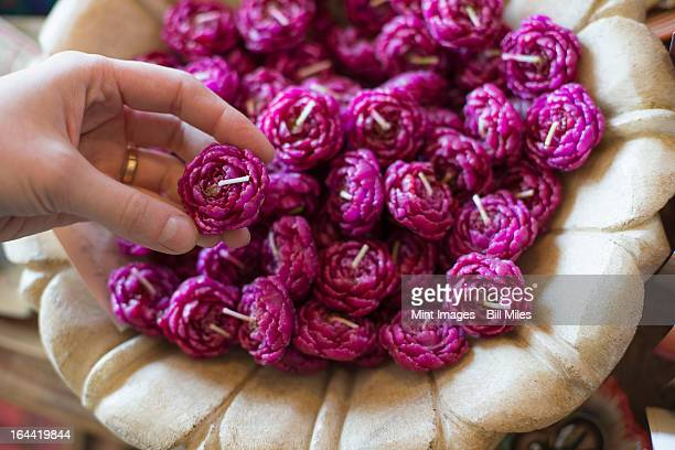 A person selecting a candle from a basket full of purple wax shaped candles.