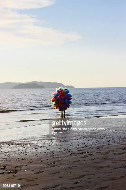 Person Selling Cotton Candies On Beach