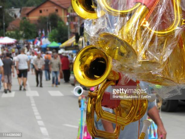 Person Selling Trumpets While Walking On Street In City