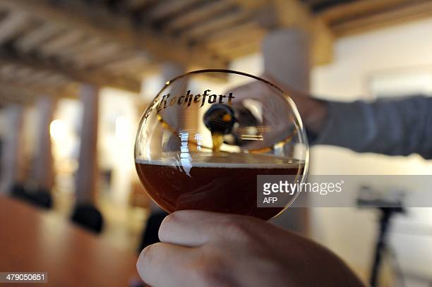 A person serves Trappist beer in a glass on February 19 2014 at the Rochefort Abbey Brewery southeast of Brussels Whether blonde amber or brown...