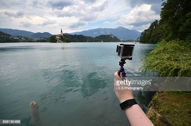 Person shooting a video with an action camera at shore of Lake Bled