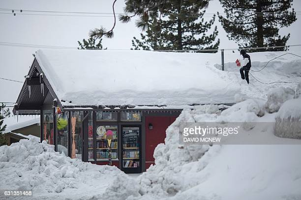 A person shovels snow from a roof in Mammoth Lakes California January 9 2017 as a series of strong storms moves through the western US state / AFP /...