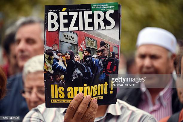 A person shows the front cover of a local newspaper featuring a manipulated photograph the original of which was taken by a photographer of Agence...