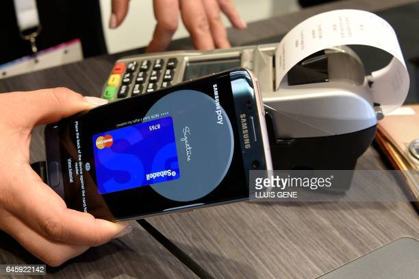 A person shows the Samsung Pay system on the first day of the Mobile World Congress in Barcelonaon on February 27 2017 in Barcelona Phone makers will...
