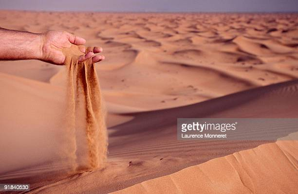 Person sifting sand through hand