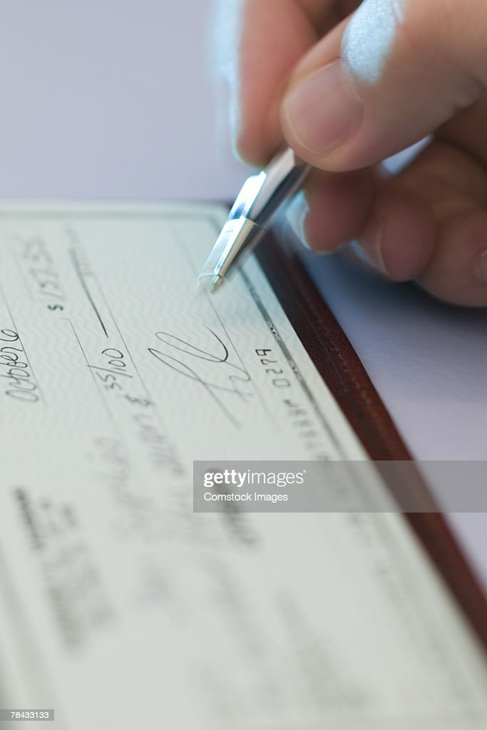 Person signing check : Stockfoto